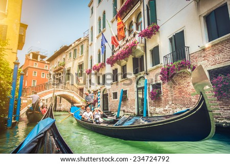 Gondolas on canal in Venice, Italy with retro vintage Instagram style filter and lens flare effect - stock photo
