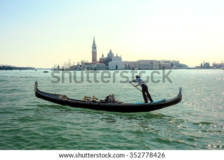 Gondolier in a gondola rides on Canal Grande in a hat with a blue ribbon and a typical striped singlet, Basilica in the background, Venice, Italy. - stock photo