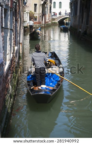 Gondolier maneuvers gondola down typical scene from a small canal in Venice with gondolas - stock photo