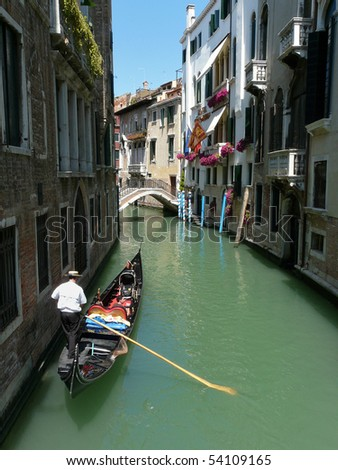 Gondolier paddling his gondola through a small channel in Venice, Italy. - stock photo