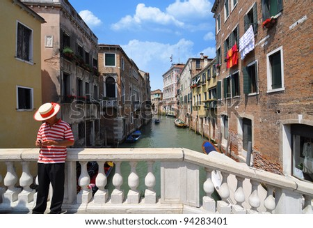 Gondolier with a striped shirt on a bridge over a canal in Venice, Italy.