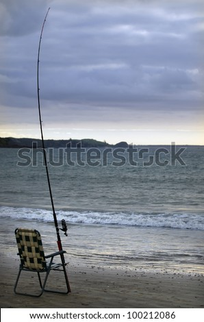 Gone Fishing - An empty chair beside a fishing rod at the beach during sunset. - stock photo