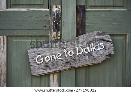 Gone to Dallas sign on old green door. - stock photo