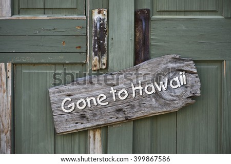 Gone to Hawaii sign on old green doors. - stock photo
