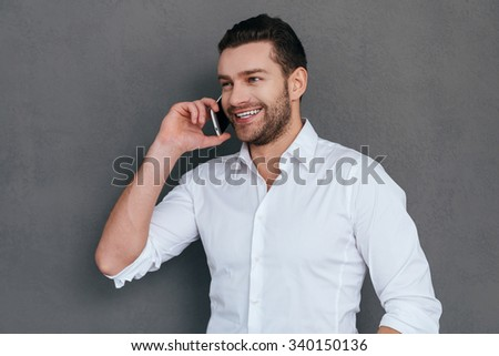 Good business talk. Handsome young man talking on the mobile phone and smiling while standing against grey background  - stock photo