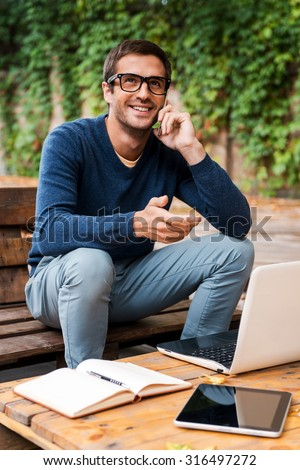 Good business talk. Happy young man talking on the mobile phonewhile sitting at the wooden table outdoors - stock photo