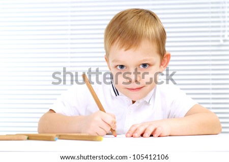 Good Caucasian male sitting at the table draws on a light background - stock photo