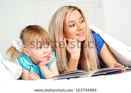 Good caucasian mother and daughter lying on the bed with a book