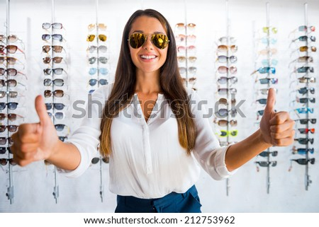 Good choice. Beautiful young woman in sunglasses showing her thumbs up and smiling while standing in optic store  - stock photo