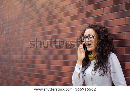 Good conversation. Attractive young woman in shirt and bowtie talking on smartphone and smiling while standing near brick wall. - stock photo