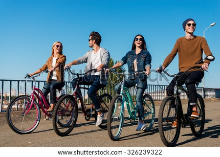 Good day for a ride. Full length of four young people riding their bicycles and smiling - stock photo