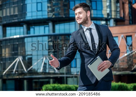 Good day! Successful smiling businessman standing in the street and meets Colleges shaking his hand. Businessman smiling directly at the camera while holding a tablet in hand