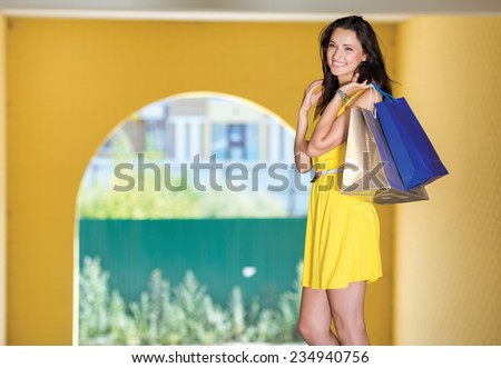 Good deal on shopping sales. Attractive young women is standing with shopping bags on the street and smiling, while looking forward - stock photo