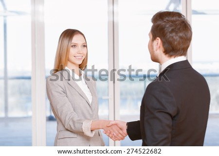 Good deal. Young businesswoman and businessman shaking hands in the office