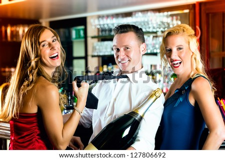 Good friends - bartender and women - with a large magnum bottle champagne at bar having fun, she pulls on his tie - stock photo