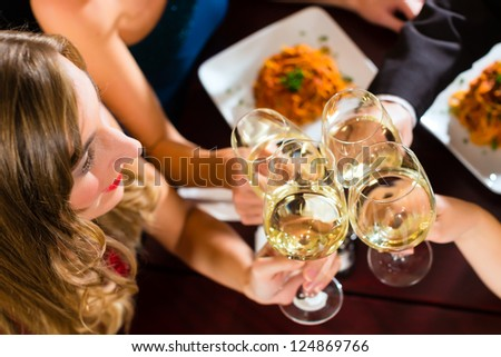 Good friends for dinner or lunch in a fine restaurant, clinking glasses - stock photo