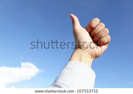 good hand gesture close up with blue sky and white cloud - stock photo