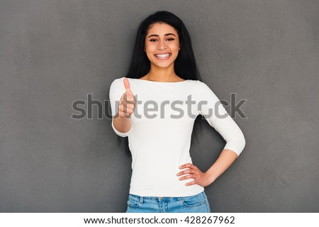 Good job! Attractive young African woman showing her thumb up and looking at camera with smile while standing against grey background - stock photo