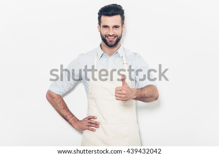 Good job! Confident young handsome man in apron keeping arms crossed and smiling while standing against white background  - stock photo