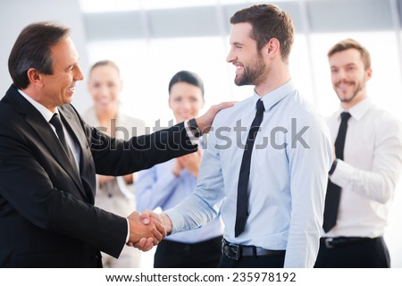 Good job! Two cheerful business men shaking hands while their colleagues applauding and smiling in the background - stock photo
