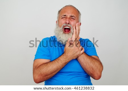Good-looking bearded man with opened mouth is touching his cheek as if having severe toothache isolated against white background