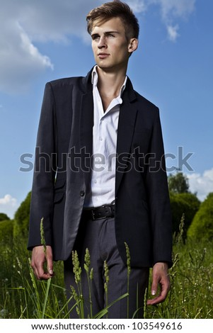 Good looking beautiful young man in suit posing outdoor - stock photo