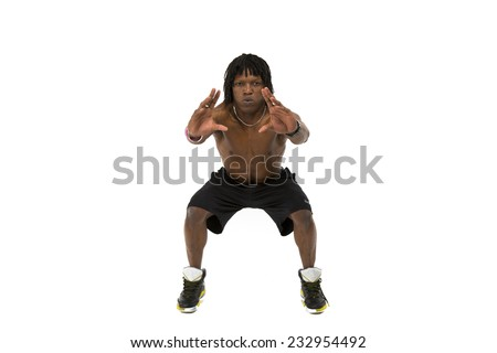 Good looking black man with dreadlocks working out topless wearing all black exercise shorts in a squat position with his arms out facing the front - stock photo