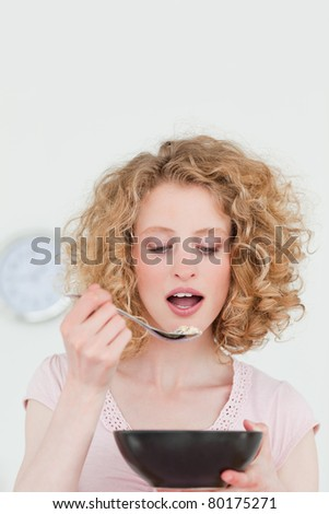 Good looking blonde woman eating a bowl of cereals in the kitchen in her apartment - stock photo