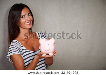 Good-looking brunette lady holding a moneybox - grey texture background