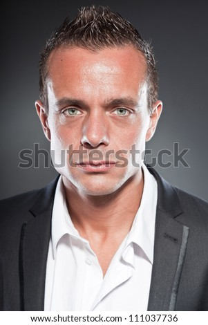 Good looking business man blue eyes and short blond hair. Tough guy. Wearing white shirt and black jacket.