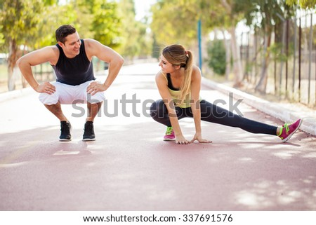 Good looking couple doing some stretching exercises as part of their workout outdoors  - stock photo