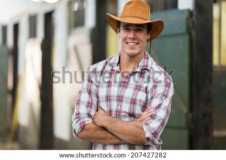 good looking cowboy with arms crossed in stable - stock photo