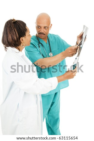 Good-looking doctors discussing a patient's x-rays.  Isolated on white. - stock photo