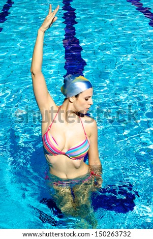 Good looking female model in water exercizing synchronized swim