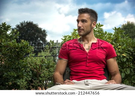 Good looking, fit male model relaxing sitting on bench outdoors, looking to a side - stock photo
