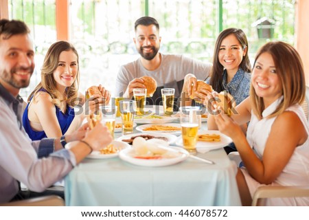 Good looking friends sitting together at a table, eating burgers and having fun during a barbecue in a patio - stock photo