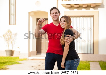 Good looking Hispanic young couple holding the keys to a house they just bought - stock photo