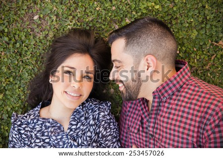 Good looking Hispanic young couple in love relaxing at a park - stock photo
