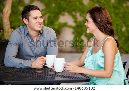 Good looking Latin couple drinking coffee and smiling on their first date at a restaurant - stock photo