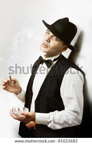 Good looking man dressed like a gangster smoking cigar - stock photo