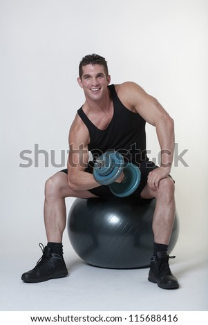 good looking man sitting on a gym ball doing dumbbell curls - stock photo