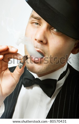 Good looking man with cigar dressed like old fashion gangster - stock photo