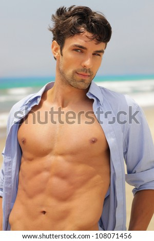 Good-looking man with seductive expression with open shirt revealing sexy body - stock photo