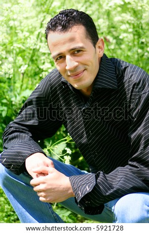 Good looking mediterranean man in black shirt and casual jeans outdoors. - stock photo