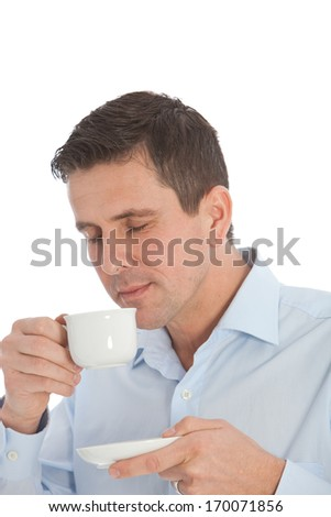 Good looking middle-aged man savouring the aroma of a cup of fresh hot coffee during a business break smiling with his eyes closed in enjoyment