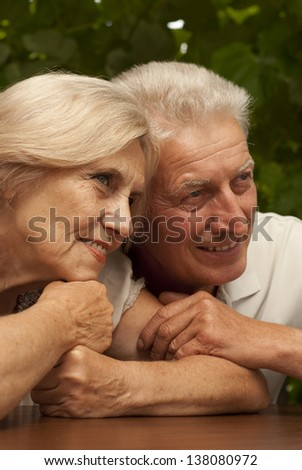 Good-looking older couple sitting at a table at home on the veranda - stock photo