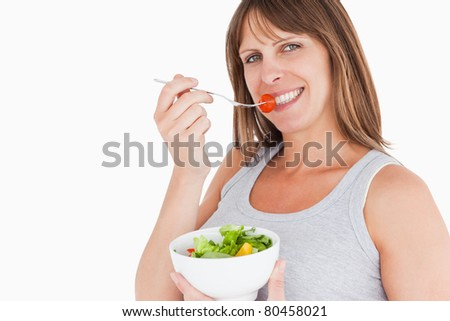 Good looking pregnant woman eating a cherry tomato while holding a bowl of salad against a white background - stock photo