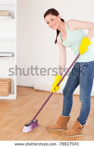 Good looking red-haired woman sweeping the floor at home - stock photo