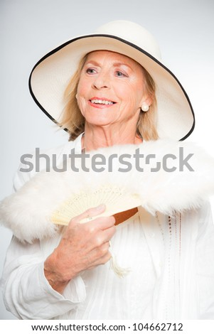 Good looking senior blond woman isolated on white background. Dressed in white and wearing white summer hat. Expression and emotion. Studio shot. - stock photo