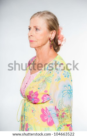 Good looking senior blond woman isolated on white background. Wearing colorful dress with flower pattern. Expression and emotion. Studio shot.